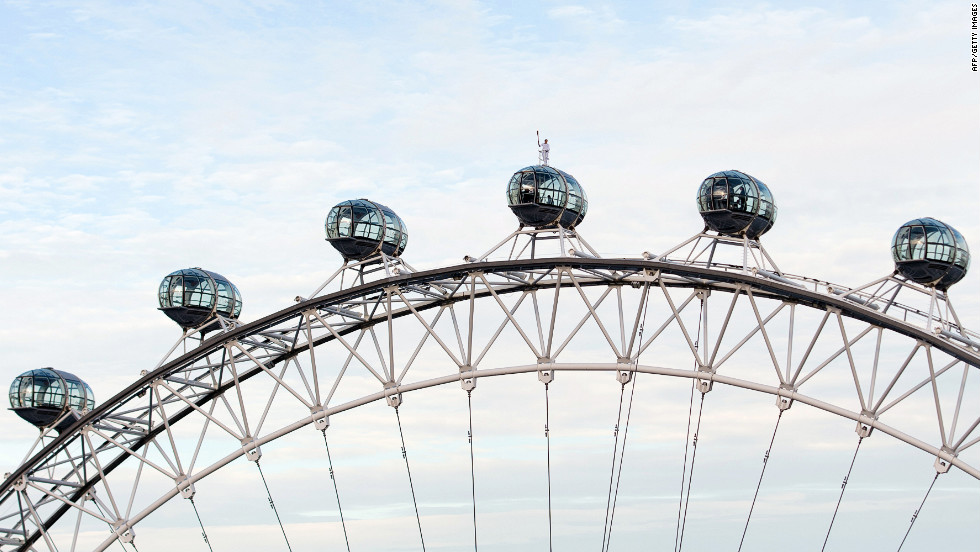 Explorer Amelia Hempleman-Adams carries the Olympic torch as she stands on the roof of a pod on the London Eye in central London on Sunday, July 22.