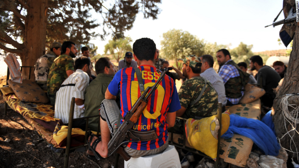 "An armed Syrian rebel wearing the jersey of FC Barcelona rests with comrades near the northern city of Aleppo on Sunday. The rebel Free Syrian Army announced the start of the battle to ""liberate"" Aleppo, Syria's commercial hub and a traditional bastion of President Bashar al-Assad's regime."