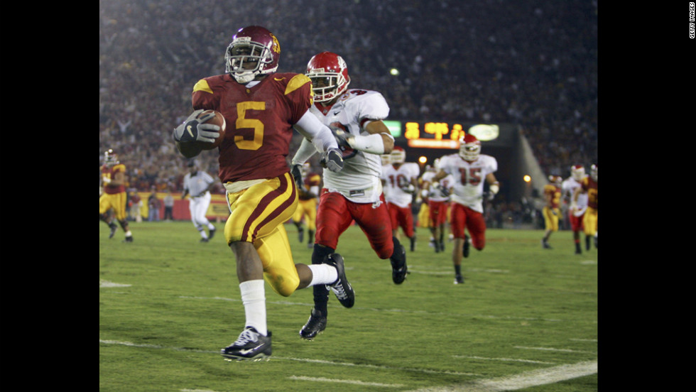 Reggie Bush of the University of Southern California carries the ball past Fresno State's Matt Davis in 2005. The NCAA announced sanctions in June 2010 against USC, finding that Bush and basketball star O.J. Mayo had received lavish gifts. Bush voluntarily forfeited his Heisman Trophy, while USC was given four years' probation, stripped of 30 scholarships and had to vacate 14 wins, including a national championship.
