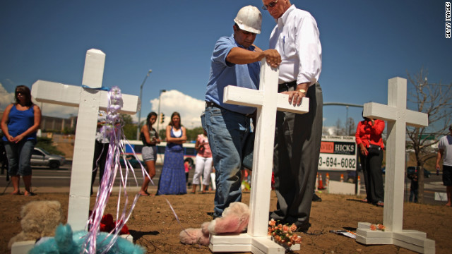Zanis left 12 crosses to remember those killed in the Aurora, Colorado, theater shooting. Here, he prays with Aurora Mayor Steve Hogan.