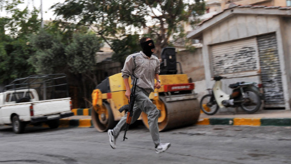 A Syrian rebel runs in a street of Selehattin during an attack on the municipal building on July 23, 2012.