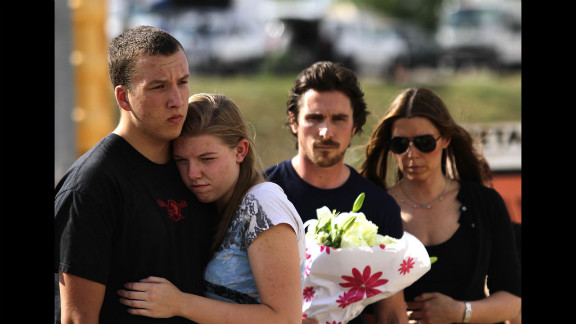 """A couple embraces as """"Dark Knight Rises"""" star Christian Bale and his wife, Sandra Blazic, wait to place flowers at the memorial on Tuesday."""
