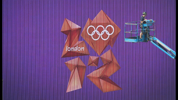 The London Olympics logo in the equestrian arena in Greenwich, London, is seen behind a worker on a lift.