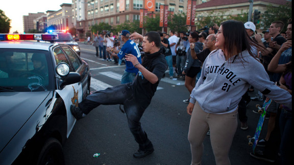 A man kicks a passing police car during a protest against Diaz's shooting.