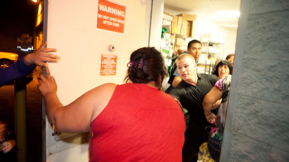 People seek shelter in the back room of a Starbucks as police and protesters clash.