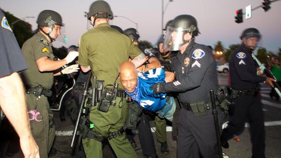Police take a protester into custody.