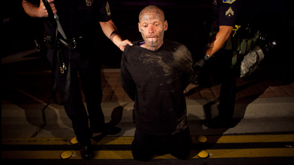 Police take a man into custody during the protest.