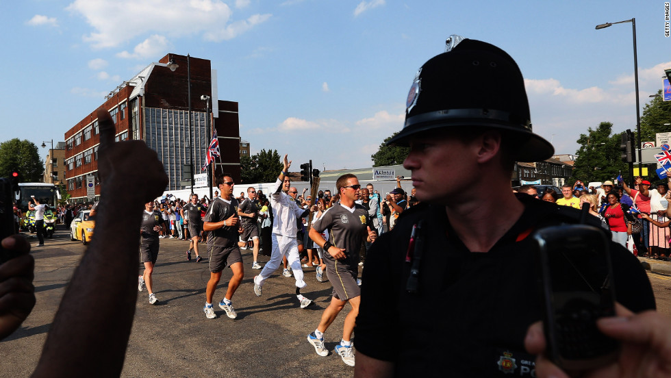 Torchbearer Scott Moorhouse, a Paralympic javelin thrower, runs with the Olympic flame along Tottenham High Road in London on Wednesday, July 25.