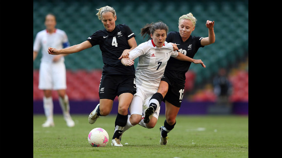 Katie Hoyle, left, of New Zealand and teammate Betsy Hassett challenge Karen Carney of Great Britain during their match in the first round of women