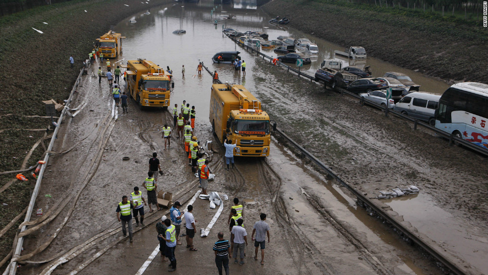 Municipal workers try to clear water on a section of the Beijing-Hong Kong-Macau expressway, where more than 80 cars were submerged on Monday, July 23, in Beijing.