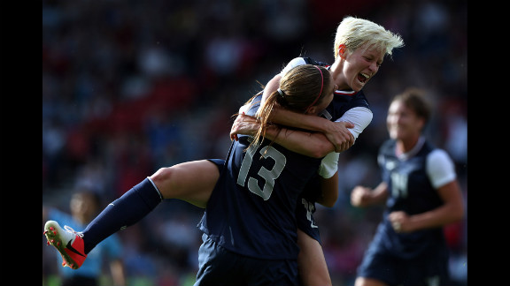 U.S. player Megan Rapinoe jumps on teammate Alex Morgan, No. 13, after Morgan scored during their Group G Olympic women