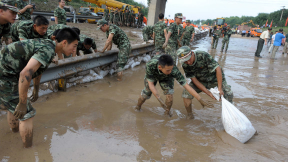 Soldiers try to clear water on a section of the Beijing-Hong Kong-Macao expressway on July 23, 2012 in Beijing, China.
