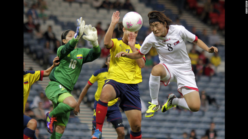 North Korea's Jon Myong Hwa, in white, vies with Colombia's Sandra Sepulveda, in green, and Orianica Velasquez , in yellow, during first-round women's soccer play at Hampden Park on July 25.