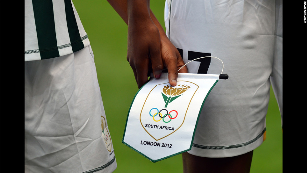 South African footballers hold a pennant as they line up before their first-round women's soccer match against Sweden on July 25 at The City of Coventry Stadium in Coventry, England.