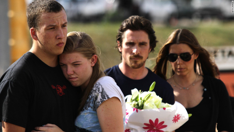 A couple at the memorial site embraces in front of Bale and his wife.