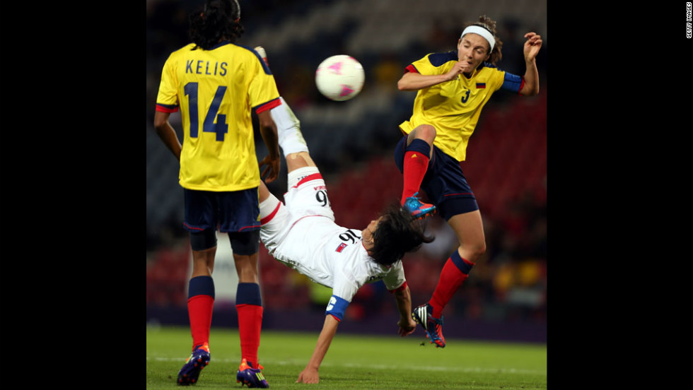 Kim Song Hui of North Korea executes a bicycle kick while challenged by Natalia Ariza of Colombia during the first-round women's football competition at Hampden Park  on Wednesday, July 25, in Glasgow, Scotland.