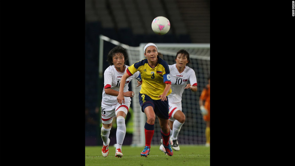 Hazleydi Rincon of Colombia and Kim Song Hui of North Korea chase the ball in a first-round women's football match.