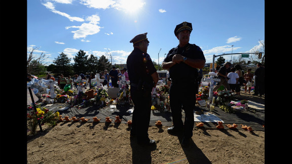 Kevin Flynn, left, Aurora Police top brass division chief, and Cmdr. Jack Daluz visit the makeshift memorial.