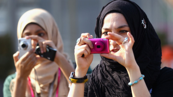 Spectators take pictures Thursday at the Olympic Village in London.