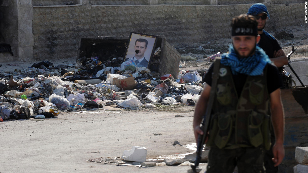 A damaged portrait of President Bashar al-Assad sits among piles of debris at a checkpoint manned by Syrian rebels in Aleppo on Wednesday.