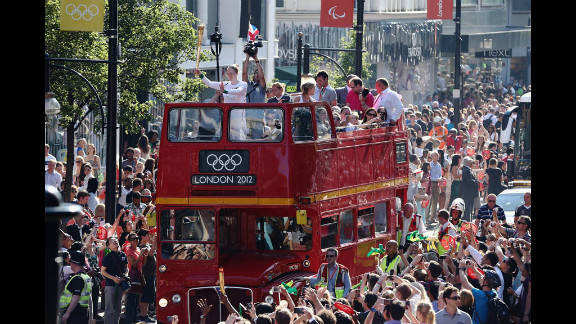An open double-deck bus carries the Olympic torch down Oxford Street  on Thursday in London.