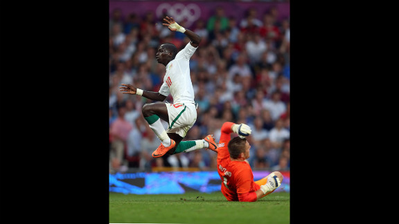 Sadio Mane of Senegal leaps over goalkeeper Jack Butland of Great Britain during the first-round men