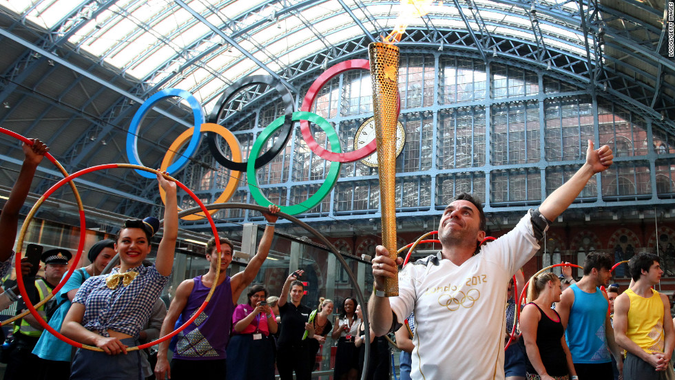 Torchbearer Daniel Mccubbin holds the Olympic flame inside St. Pancras International Railway Station on Thursday, July 26.