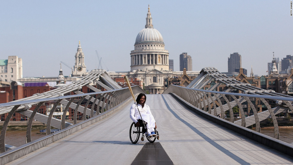 Wheelchair basketball player Adedoyin Adepitan of Great Britain carries the Olympic flame Thursday over Millennium Bridge in front of St. Paul's Cathedral in London.