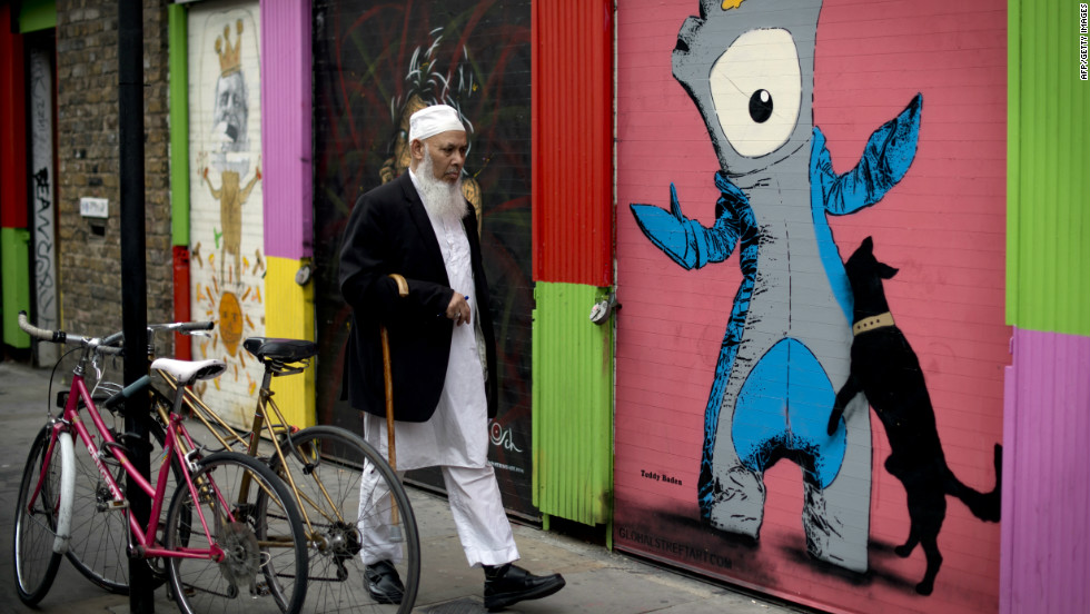 A man walks past graffiti depicting 'Mandeville' (R), one of the official Olympic mascots, in east London two days before the start of the Games.