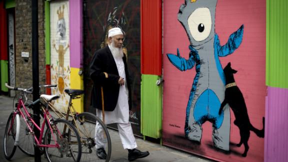 A man walks past graffiti depicting