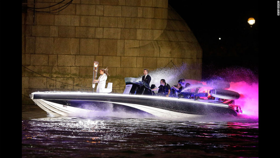 "David Beckham passes under Tower Bridge driving a speedboat named ""Max Power,"" which carries the Olympic Torch."
