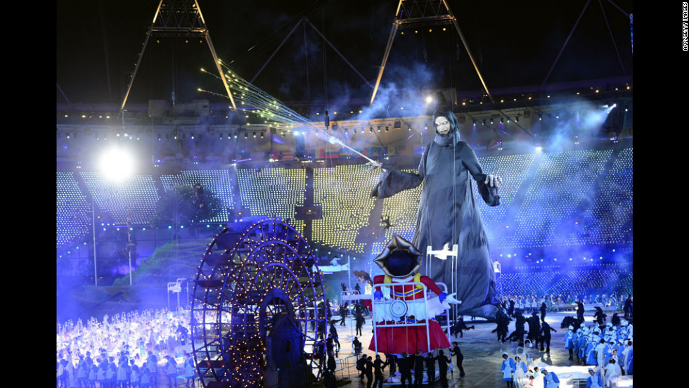 "Giant puppets depicting Lord Voldemort, center, from the Harry Potter books and the Child Catcher from ""Chitty Chitty Bang Bang"" swirl around the stage in the opening ceremony."
