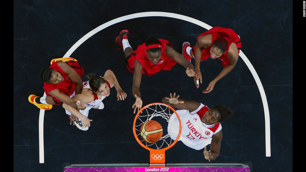 Angola's Nadir Manuel, No. 14, center, follows through on her shot against Turkey's Quanitra Hollingsvorth, No. 12, and Turkey's Saziye Ivegin, No. 14.
