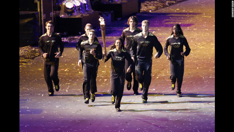 Young athletes carry the Olympic torch toward the cauldron during the opening ceremony.