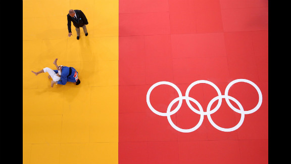 Sofiane Milous of France, in white, competes with Hovhannes Davtyan of Armenia during the men's judo event.