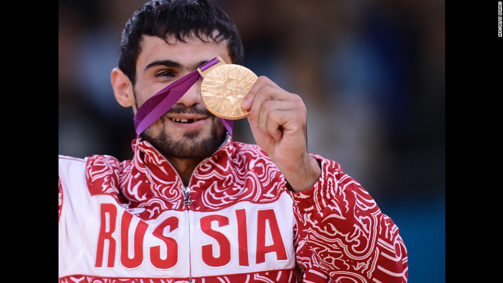 Russia's gold medalist Arsen Galstyan poses on the podium of a men's judo event.