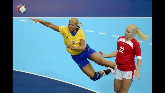 Sweden's pivot Ulrika Agren, left, shoots under the look of Denmark's leftback Trine Troelsen during a women's preliminary handball match.