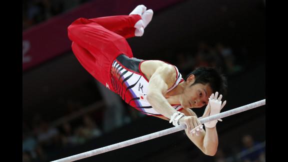 Japanese gymnast Kazuhito Tanaka competes on the horizontal bar during the men's artistic gymnastics qualification event.