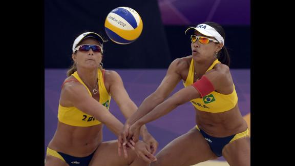 Brazil's Larissa Franca, left, and Juliana Silva both go for the ball during the women's beach volleyball preliminary game against Natacha Rigobert and Elodie Li Yuk Lo of Mauritus.