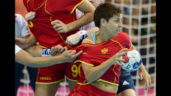 Montenegro's pivot Ana Dokic vies with her competitors from Great Britain during a women's handball preliminary match.