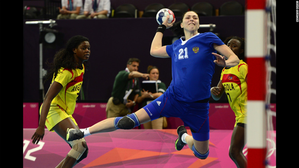 Russia's leftback Victoria Zhilinskayte, right, jumps to shoot during a preliminary round handball match against Angola.