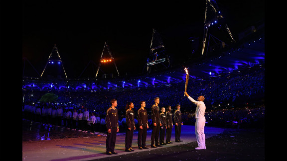 Torchbearer Sir Steve Redgrave hands the Olympic flame over to the seven young athletes who represent Britain