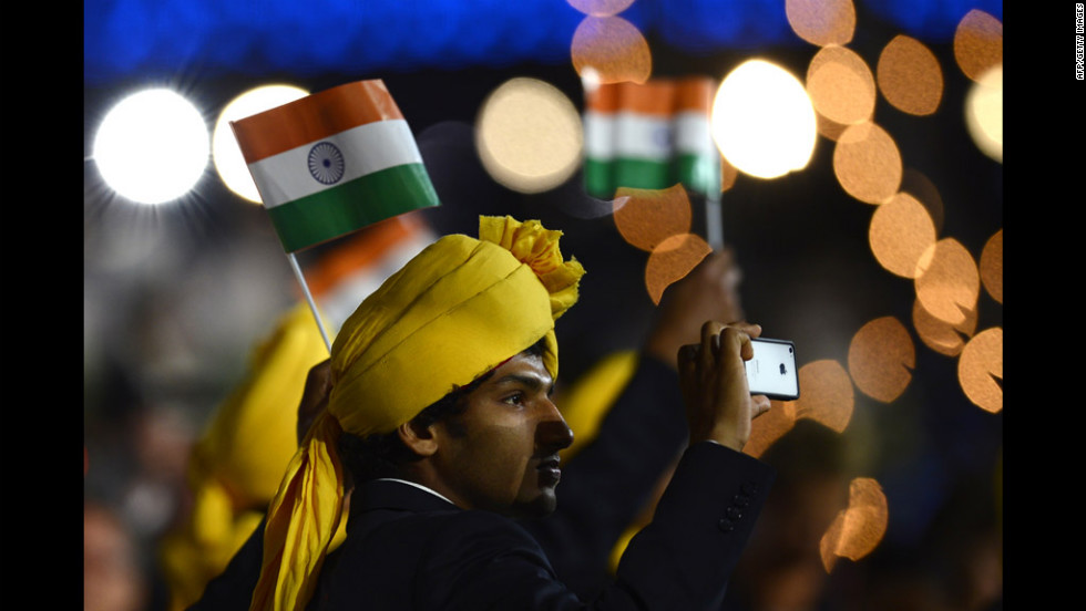 A member of India's delegation takes a picture as he parades during the opening ceremony.
