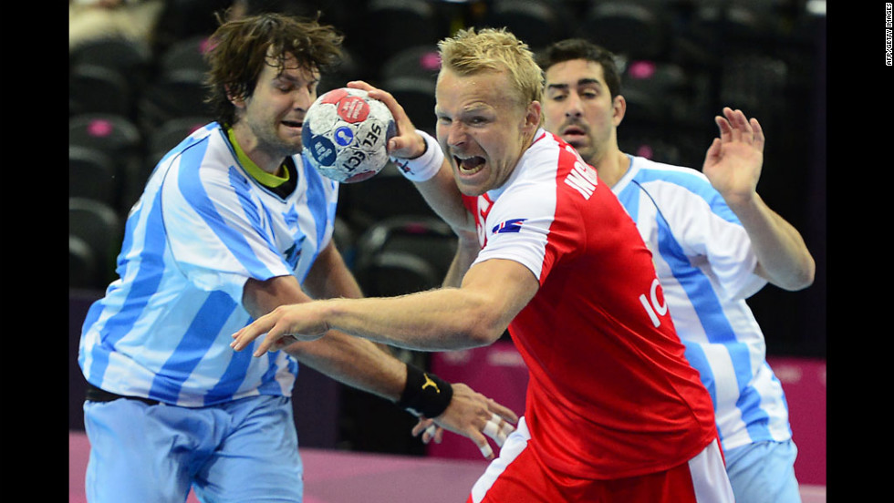 Gudjon Valur Sigurdsson of Iceland, center in red, prepares to shoot against Argentina during a men's preliminary handball match.