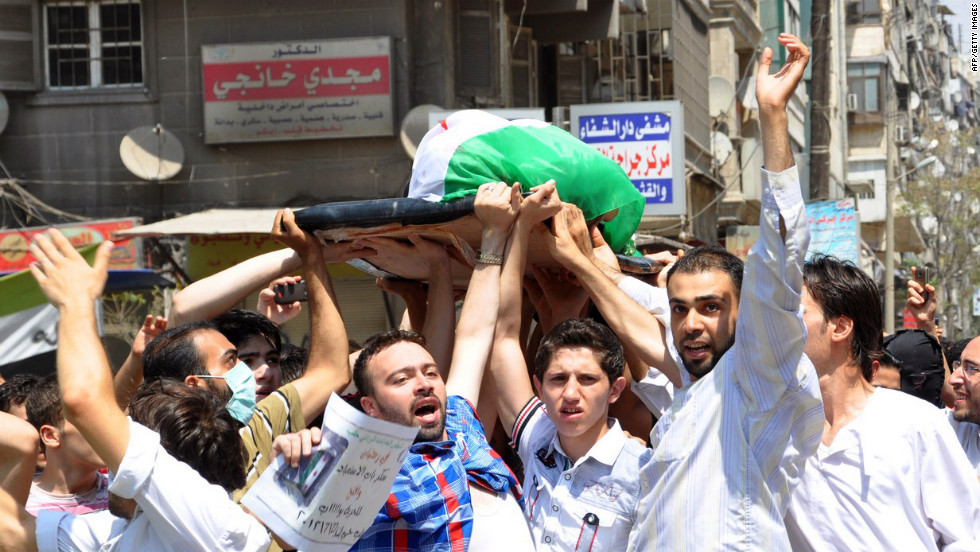 Syrians carry the body of a man allegedly killed in the bombardment of Sukari, southwest of Aleppo, by Syrian regime forces on July 27.