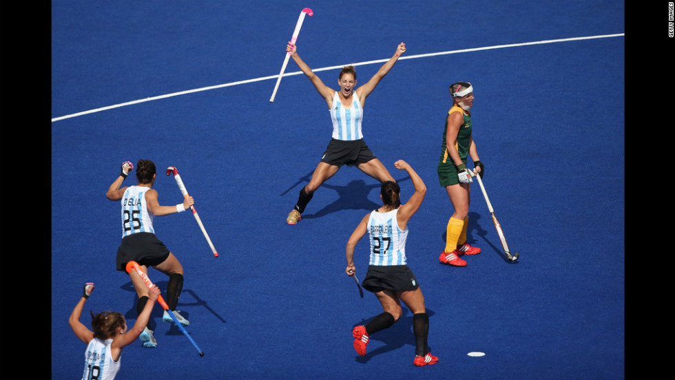 Argentina's Luciana Aymar, center, rear, and her teammates cheer after she scored the opening goal during a women's field hockey match between Argentina and South Africa