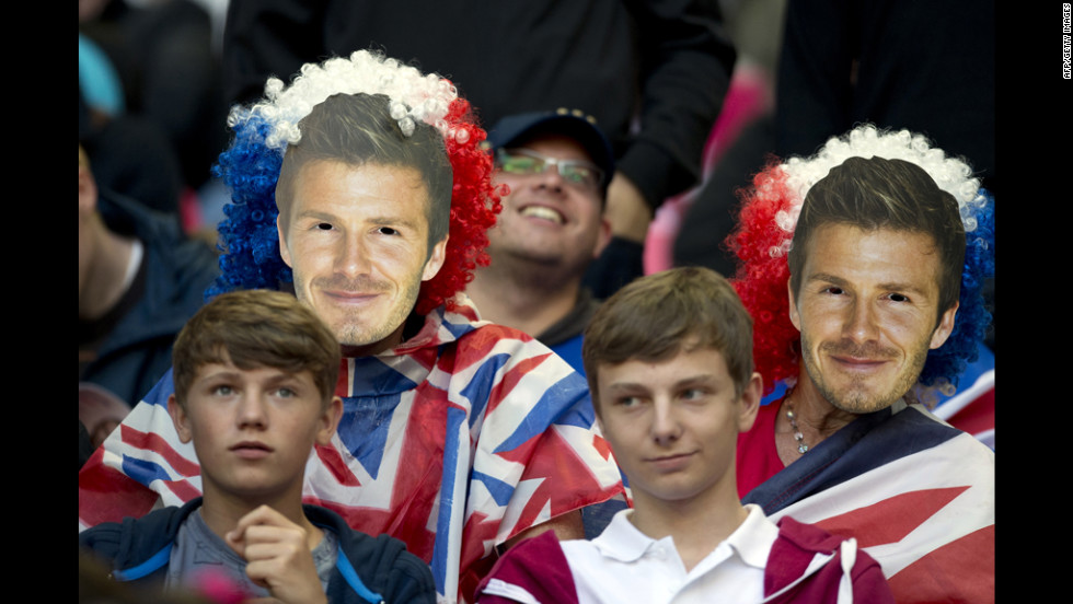 Football fans wear masks depicting Beckham at the London 2012 Olympics. He was not picked for the GB team, but played a big role in his hometown being awarded the Games.