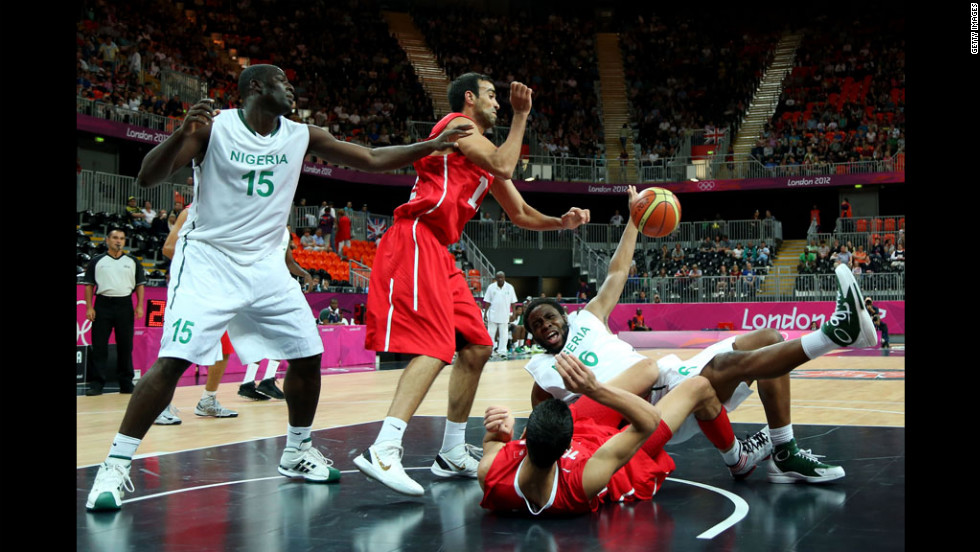Nigeria's Ike Diogu, No. 6 in white, collides with Tunisia's Salah Mejri, No. 15 in red, during their men's basketball game.