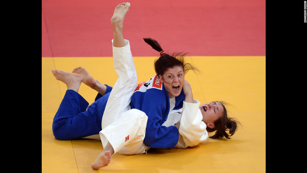 Romania's Corina Caprioriu, in blue, celebrates after defeating Marti Malloy of the United States during the women's 57-kilogram judo contest semi-final match Monday.