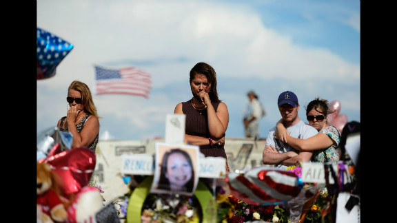 """Cynthia Davis, center, visits the roadside memorial set up for victims of the Colorado shooting massacre across the street from the Century 16 movie theater on Monday, July 30, 2012, in Aurora, Colorado. Twelve people were killed in the theater early July 20, 2012, during a screening of """"The Dark Knight Rises."""" Suspect James Holmes was taken into custody shortly after the attack. <a href=""""http://www.cnn.com/2012/07/20/us/gallery/colorado-theater-shooting/index.html"""" target=""""_blank"""">More photos: Colorado movie theater shooting</a>"""